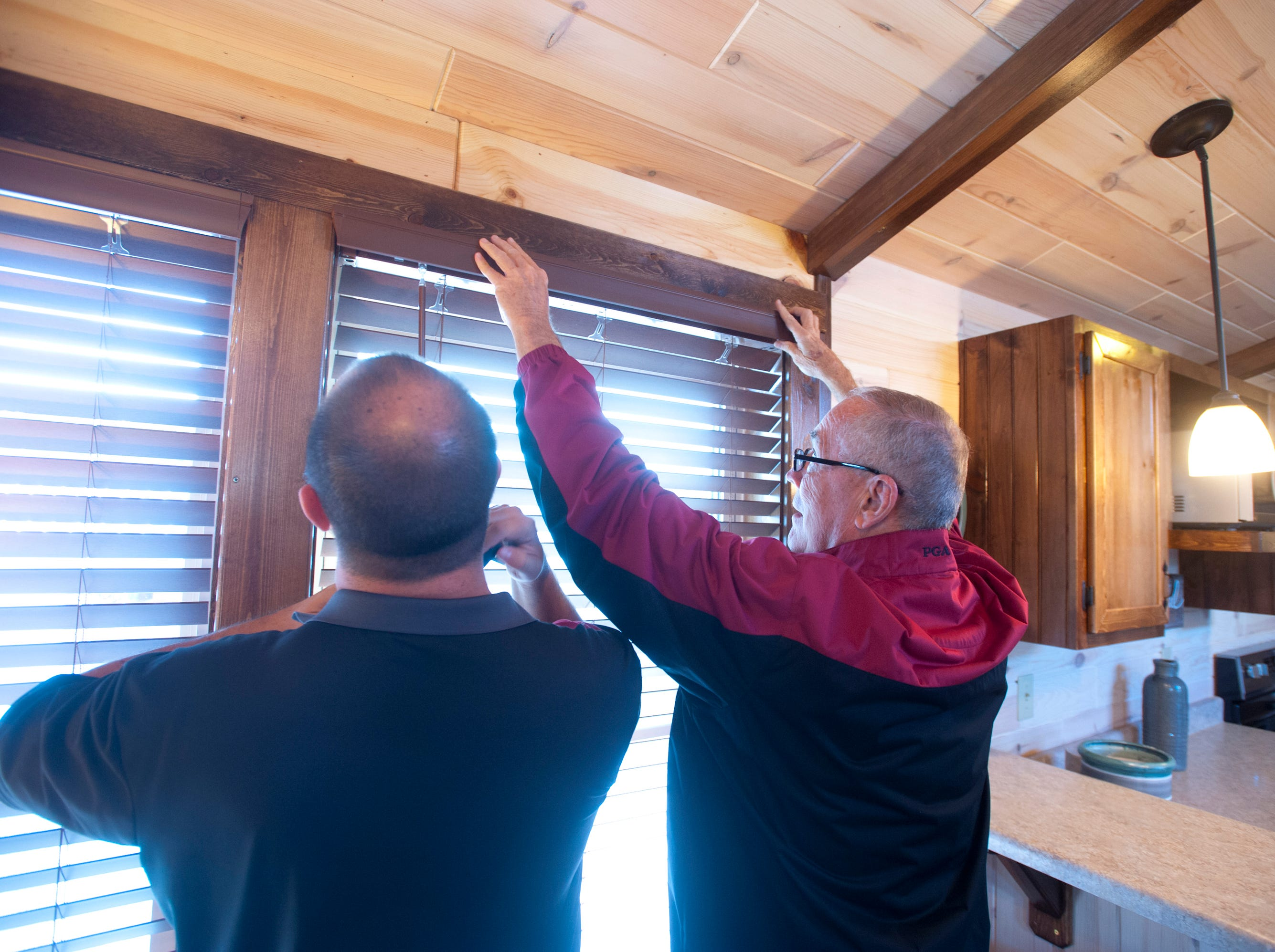 """Amish Made Cabins of Shepherdsville is making this """"White River"""" cottage, geared toward its elderly and disabled customers. Here, owner Jim White, right, and his son, Brian, left, finish off the blinds on one of the windows.September 10, 2018"""