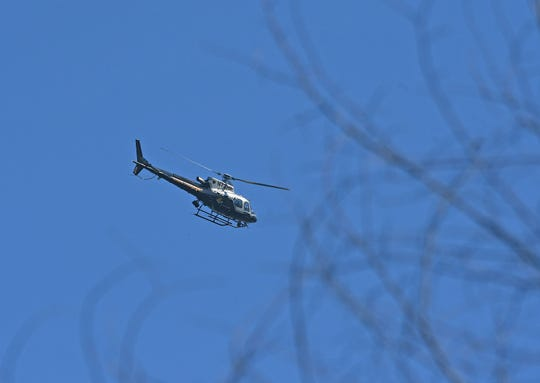 A helicopter from the Ohio Highway Patrol is piloted over the Orchard Park Road area as the search for Shawn Christy continued Tuesday afternoon.