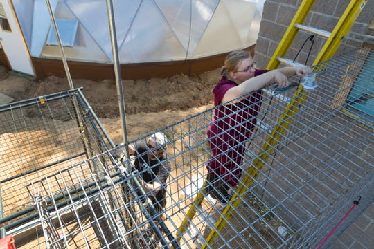 Volunteer Mike Kerwin (left) and animal caretaker Amber Zorn work on attaching a walkway that will allow primates  to exit their indoor enclosure and go into an outdoor one.