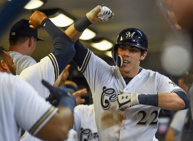 Sep 17, 2018; Milwaukee, WI, USA; Milwaukee Brewers left fielder Christian Yelich (22) celebrates in the dugout after hitting a 2-run homer in the fifth inning against the Cincinnati Reds at Miller Park. Mandatory Credit: Benny Sieu-USA TODAY Sports