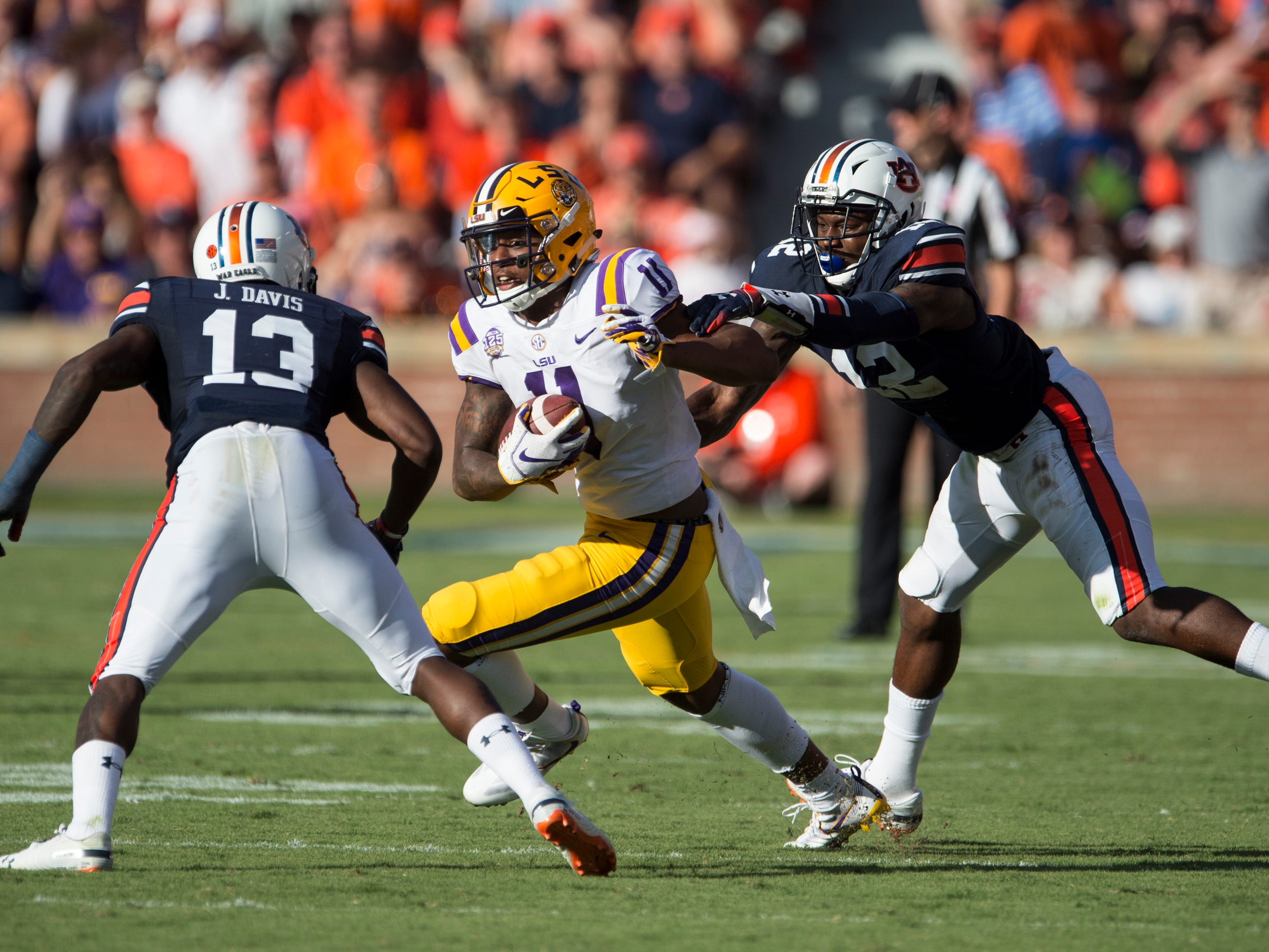 LSU's Dee Anderson (11) is tackled by Auburn's Javaris Davis (13) and Jamel Dean (12) at Jordan-Hare Stadium in Auburn, Ala., on Saturday, Sept. 15, 2018. LSU defeated Auburn 22-21.