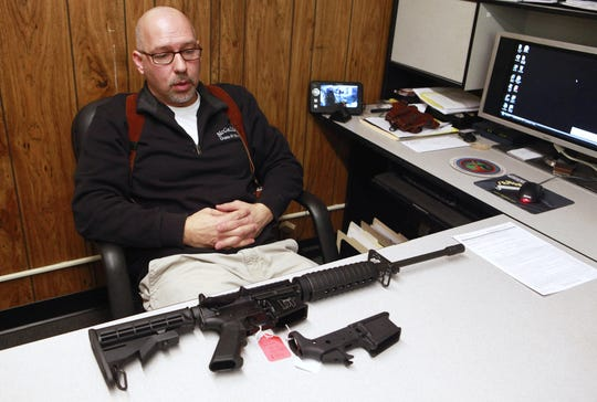 McGalliard Guns and More owner Jeff Burke is pictured in 2013 showing off an AR-15 available at his store.