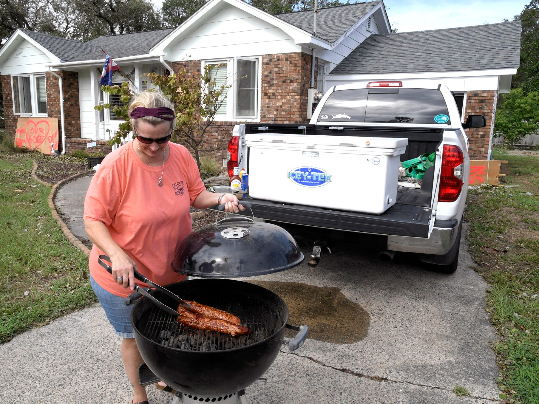 With no electricity, Leigh Bartlett cooks food on a charcoal grill for her family and neighbors in her Harkers Island driveway on Monday, Sept. 17, 2018. Bartlett heard that Harkers Island might be without power for a month.