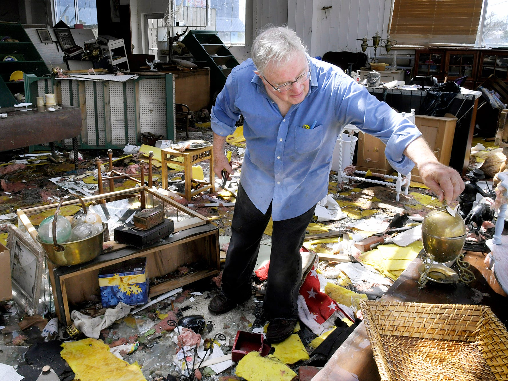 Peter Hanson helps clean up inside Seaport Antiques in Morehead City on Monday Sept. 17, 2018. Tropical Storm Florence shattered the front windows of the store over the weekend, then sucked the roof off half of the store and dropped it in the parking lot next door.