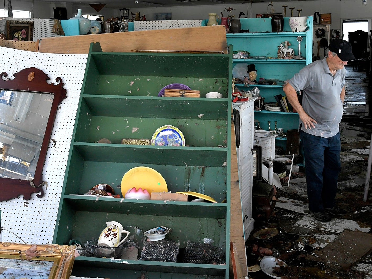 Don Thompson surveys the damage inside his Seaport Antiques store in Morehead City omn on Monday Sept. 17, 2018.  Tropical Storm Florence shattered the front windows of Seaport Antiques over the weekend, then sucked the roof off half of the store and dropped it in the parking lot next door.