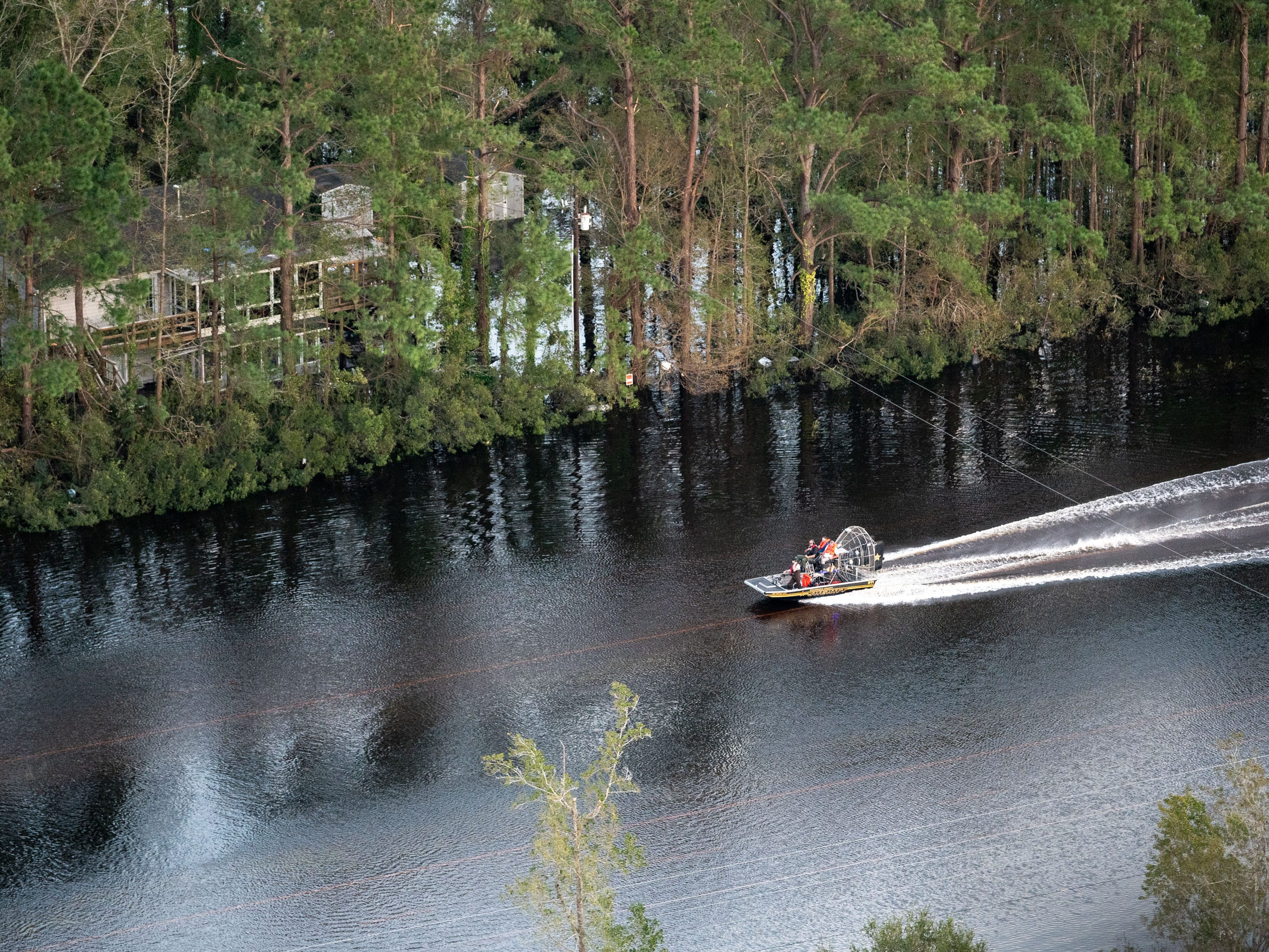 A boat passes down the flooded US-17, as seen from a Coast Guard helicopter, in Brunswick County, N.C., Monday, Sept. 17, 2018.