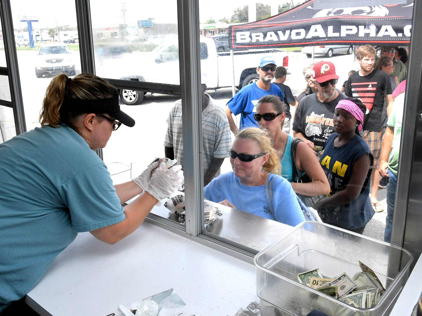 Michelle Byrum hands out hamburgers as people wait in line for free food from the Beer Army Burger Company food truck in Morehead City N.C., on Sept. 17, 2018.