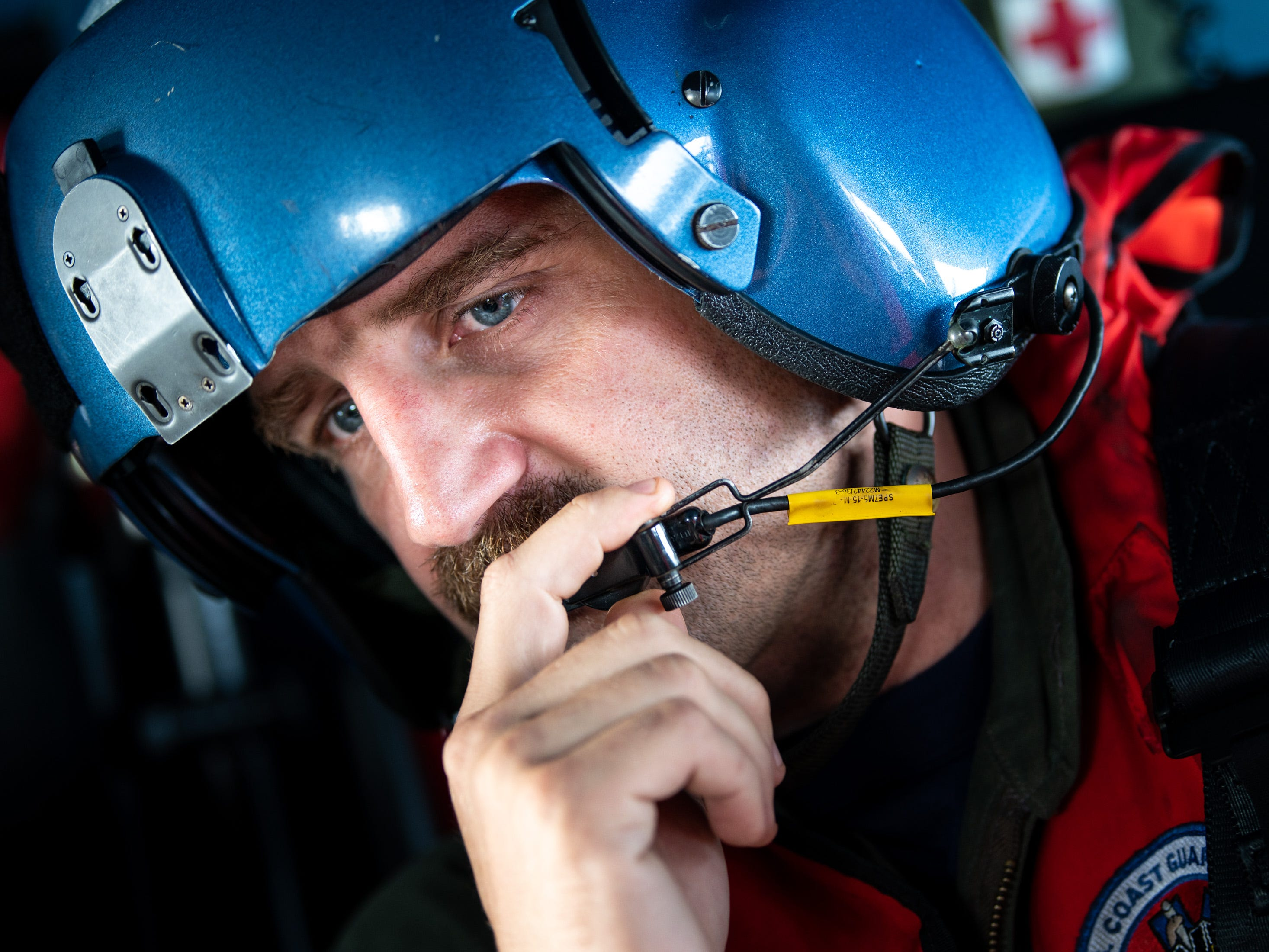 Coast Guard Rescue Swimmer AST Scott Garren speaks to other crew members through his microphone as their helicopter is diverted from flood relief efforts, Monday, Sept. 17, 2018. The crew was dispatched to the Carnival Pride cruise ship, which was about 100 miles off the North Carolina shore, to medevac a 70-year-old woman who had a heart attack.