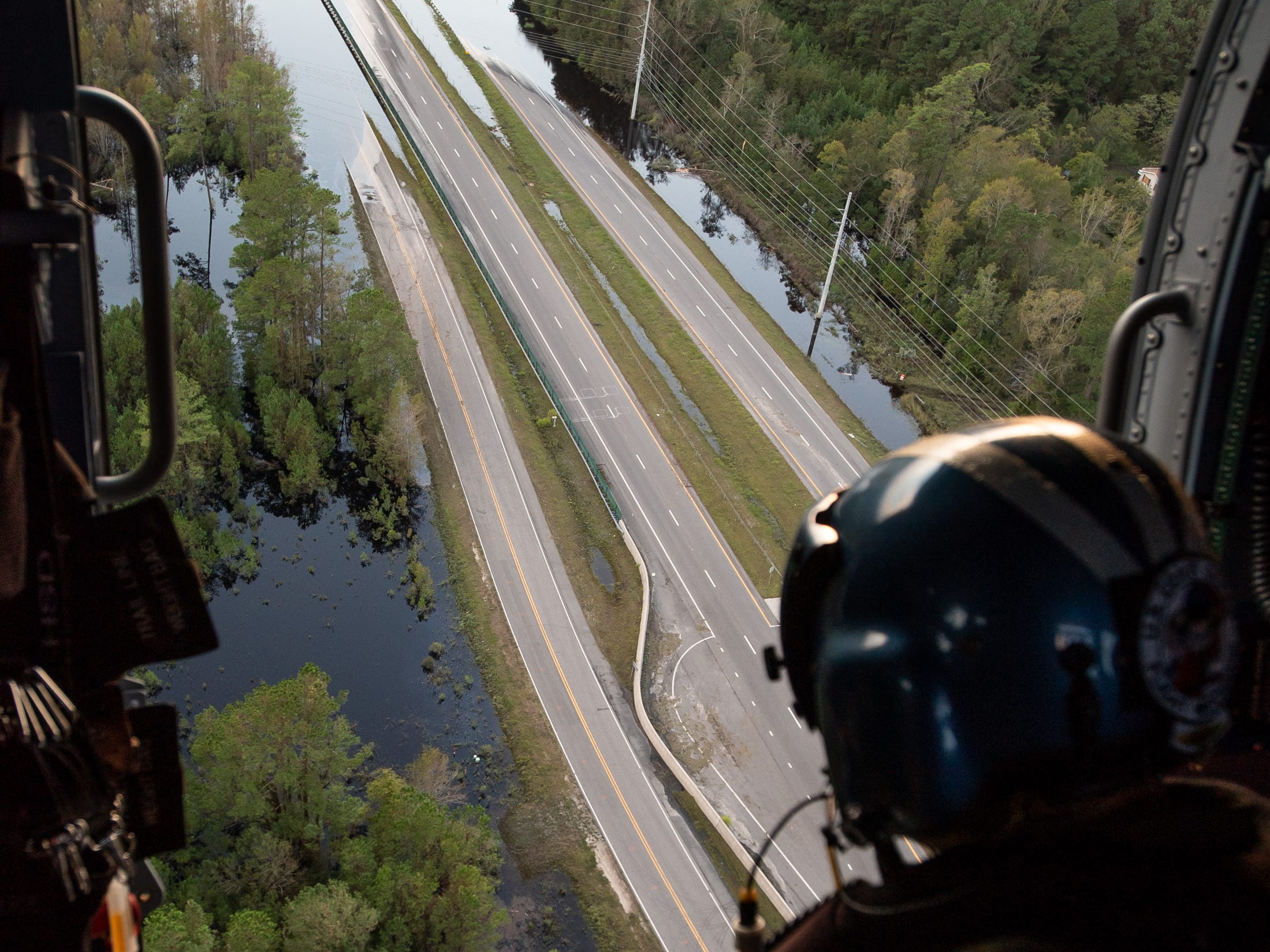 Coast Guard Flight Mechanic AMT Nick Gilkinson looks at the flooded US-17 from a MH-60T Jayhawk helicopter during a flood relief mission in Brunswick County, N.C., Monday, Sept. 17, 2018.