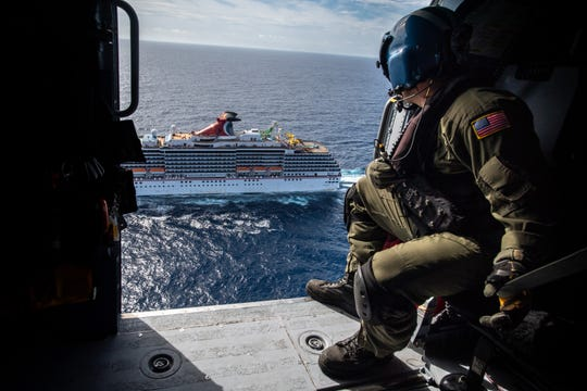 A Coast Guard flight mechanic watches as his helicopter approaches the Carnival Pride to medevac a passenger who had fallen ill on another cruise in this Gannett file photo from September.