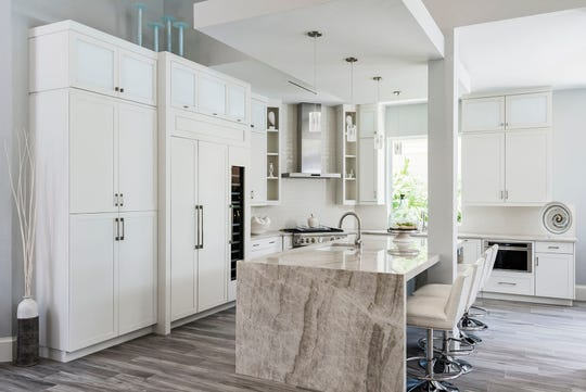 AFTER: A new dropped cantilevered soffit and cabinetry maximized storage space, while a waterfall-style island, gas range, and stainless steel hood added to produce a sleeker-looking kitchen. A new entertainment island ties the kitchen to the rest of the house.