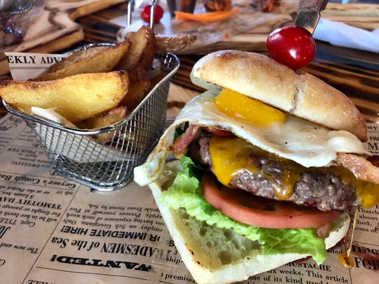 The sunrise burger is topped with bacon, cheddar cheese, lettuce, tomato and a fried egg at Western Prime Burger in North Naples.