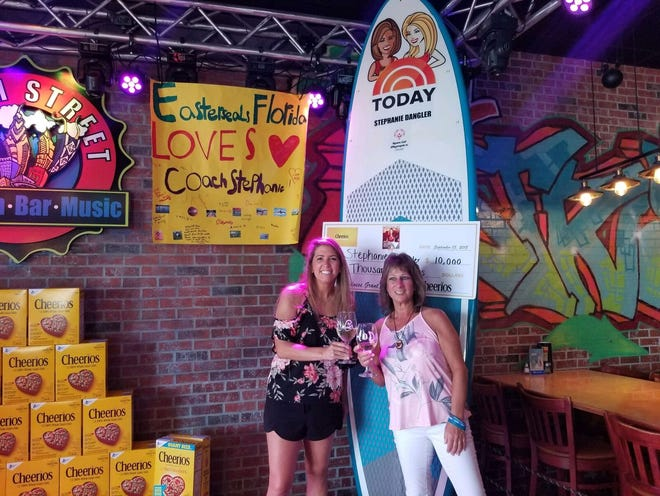"""Audra Esper, left, and Stephanie Dangler celebrate at a watch party for Dangler's segment on NBC's """"Today."""" She received the 'surprise of a lifetime' after Esper entered her in a contest. She won a custom-made paddleboard featuring the images of show hosts Hoda Kotb and Kathie Lee Gifford and a check for $10,000."""
