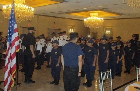 Cadets from Paterson's PAL stand at attention at the organization's recent honors banquet.