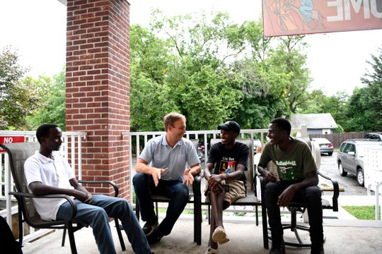 (L-R) Nshongore, Reverend Seth Kaper-Dale, Faustin, and Mugabo talk on the porch of the Reformed Church of Highland Park on Tuesday, September 18, 2018. Nshongore, Faustin, and Mugabo are all refugees from Democratic Republic of the Congo.