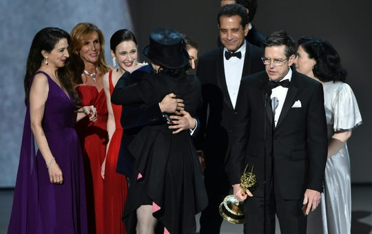 Amy Sherman-Palladino (front center) receives a hug from Michael Zegen after accepting the Outstanding Comedy Series award for 'The Marvelous Mrs. Maisel' onstage during the 70th Emmy Awards at the Microsoft Theatre in Los Angeles, California on Sept. 17, 2018.