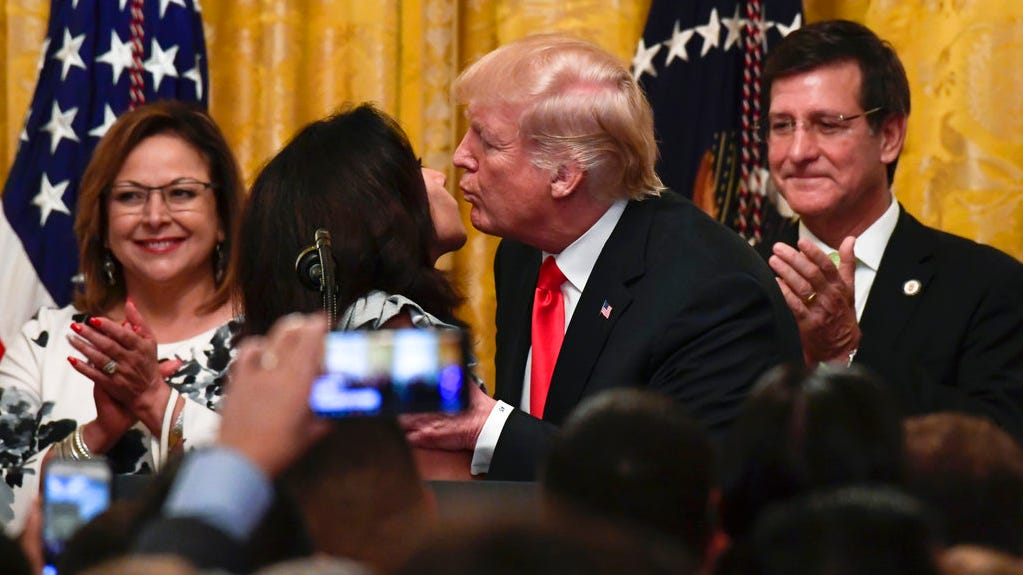 President Donald Trump, second from right, kisses Cuban-American restaurant owner Irina Vilariño, second from left, during a Hispanic Heritage Month Celebration in the East Room of the White House in Washington, Monday, Sept. 17, 2018. Luis G. Rivera Marín, Secretary of State and Lt. Governor of Puerto Rico, watches at right.