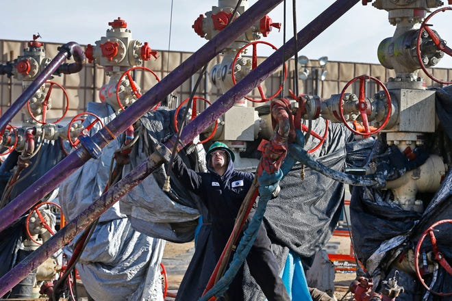 In this March 25, 2014 file photo, a worker adjusts pipes during a hydraulic fracturing operation at a well pad near Mead, Colorado. The Trump administration is moving to roll back Obama-era rules intended to reduce leaks of climate-changing methane from oil and gas facilities.