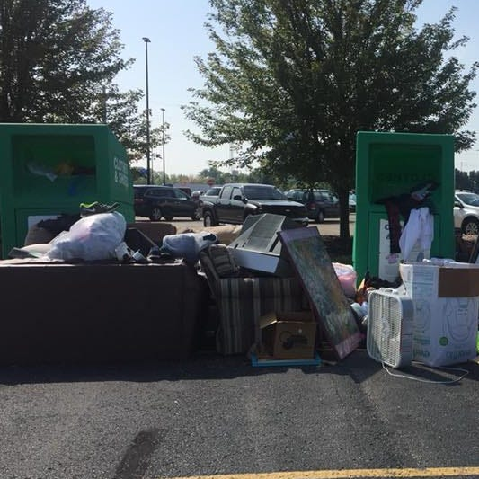 What's next for mysterious green clothing donation bins and a junk pile in a parking lot?