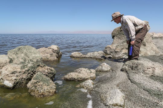 Chris Schoneman of the Sonny Bono Salton Sea National Wildlife Refuge examines the water near the Red Hill Bay restoration project site on Sept. 12, 2018.