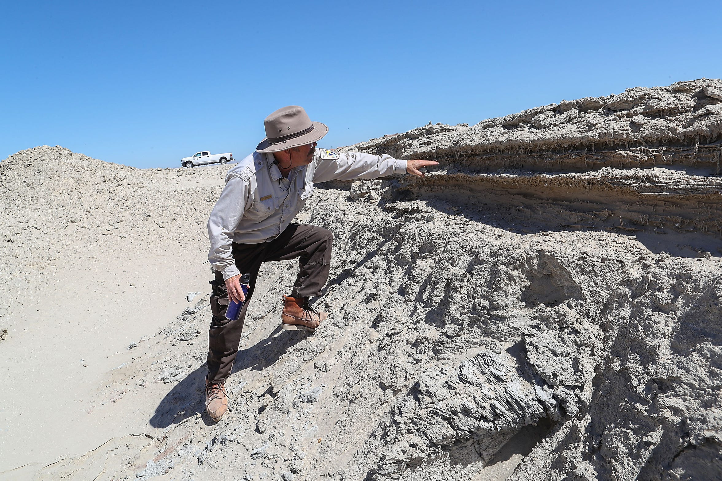 Biologist Chris Schoneman of the Sonny Bono Salton Sea National Wildlife Refuge points out the layers of sand above the clay at the Red Hill Bay restoration project site on Sept. 12, 2018.