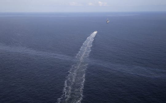In this March 31, 2015, photo, the wake of a supply vessel heading towards a working platform crosses over an oil sheen drifting from the site of the former Taylor Energy oil rig in the Gulf of Mexico, off the coast of Louisiana. Down to just one full-time employee, Taylor Energy Company exists for only one reason: to fight a Gulf of Mexico oil leak that has gone largely unnoticed, despite creating miles-long slicks for more than a decade.