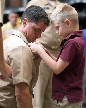Terry McConnell, a selectee for Navy chief, has his 8-year-old son, William, pin his chief's insignia on his collar during a ceremony Sept. 14 at the National Naval Aviation Museum