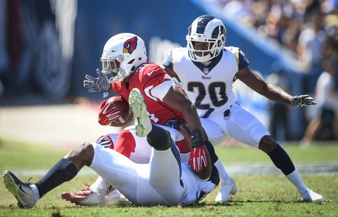 David Johnson is tackled by Cory Littleton and Lamarcus Joyner of the Los Angeles Rams at Los Angeles Memorial Coliseum on Sept. 16, 2018.