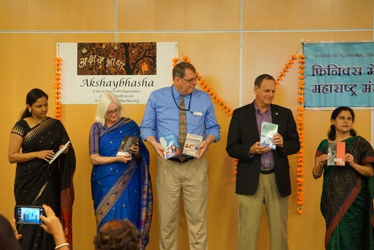 Dr. Bhagyashree Barlingay (far right) presents Marathi language books for the inauguration of the Chandler Public Library's Marathi language collection.