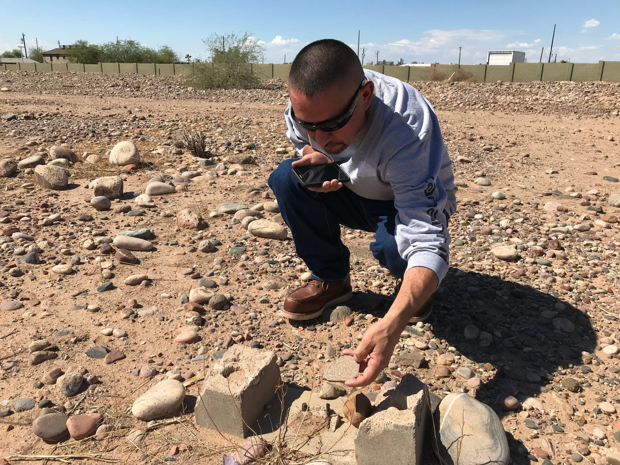 Tim Diaz, who grew up in the Sotelo-Heard neighborhood, examines the remains of a headstone that was vandalized years ago.