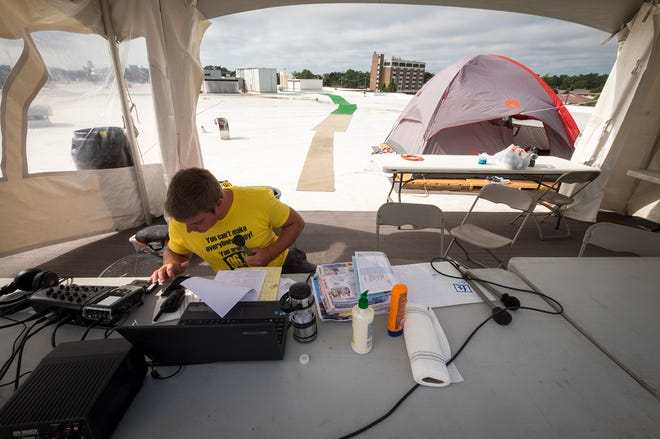 Q Country 107 WSAQ host Matt Markham checks his cell phone during a break Tuesday, Sept. 18, 2018, during the annual Community Roof-Sit for Kids on the roof of the Michigan Mutual building in downtown Port Huron. This year, Markham took over the event from fellow WSAQ host Chuck Santoni.