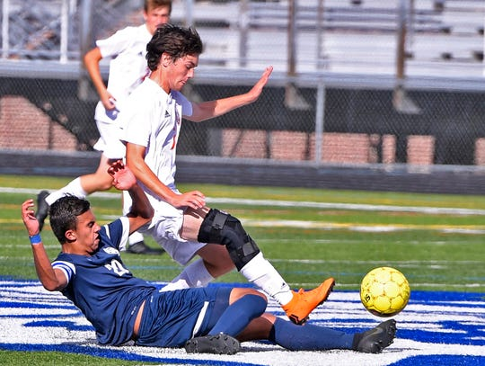 Dallastown's Gabe Wunderlich slide tackles Shane Buss of Central York, Tuesday, Sept. 18, 2018.  John A. Pavoncello photo
