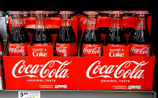 "In this Aug. 8, 2018, file photo, bottles of Coca Cola sit on a shelf in a market in Pittsburgh. The Coca-Cola Company says that it's ""closely watching"" the growth of the use of a non-psychoactive element of cannabis in wellness drinks."
