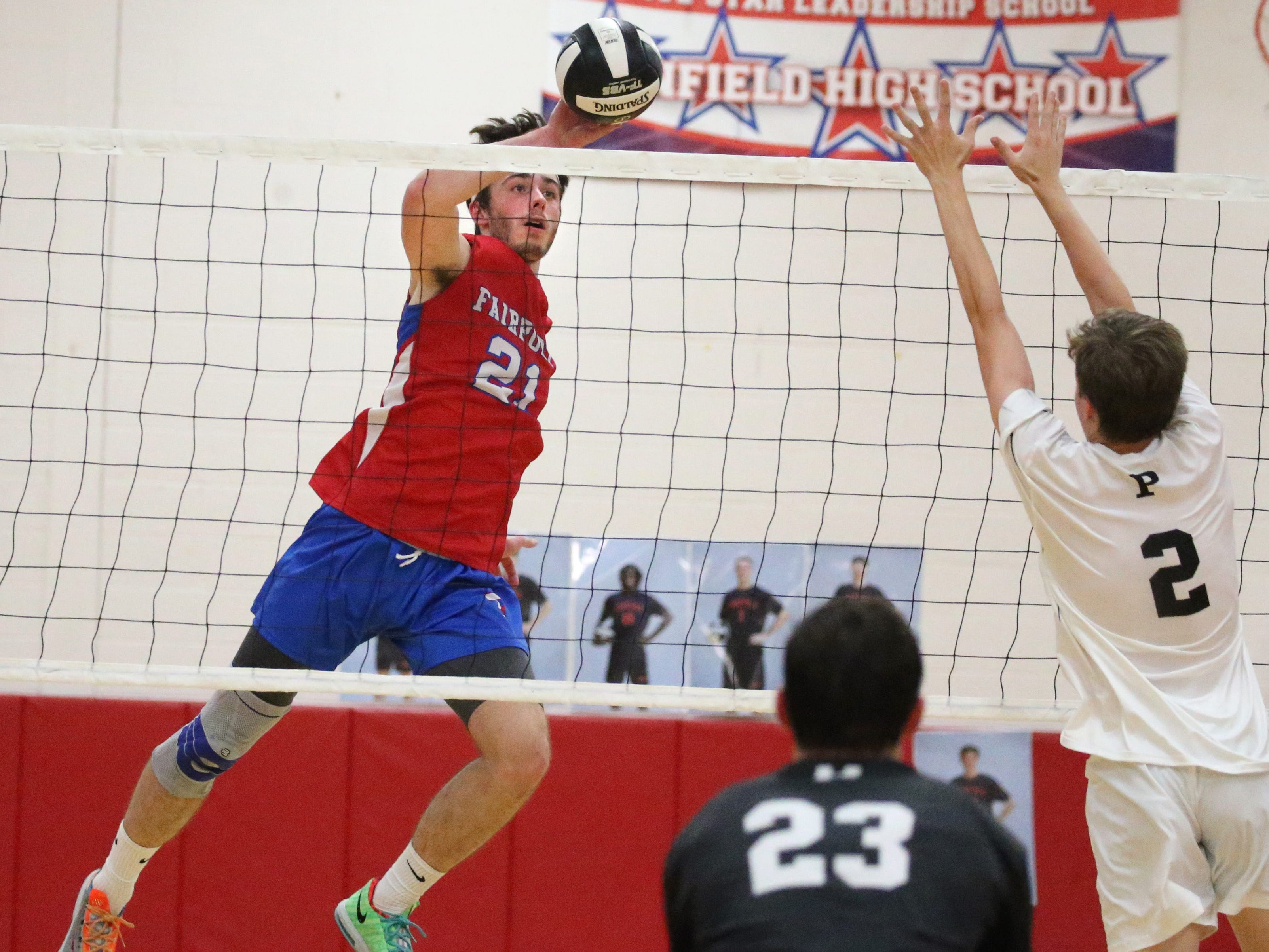 Fairport's Matt Beiter, left, pushes the ball over the net past Penfield's Jordan Klembczyk, right.
