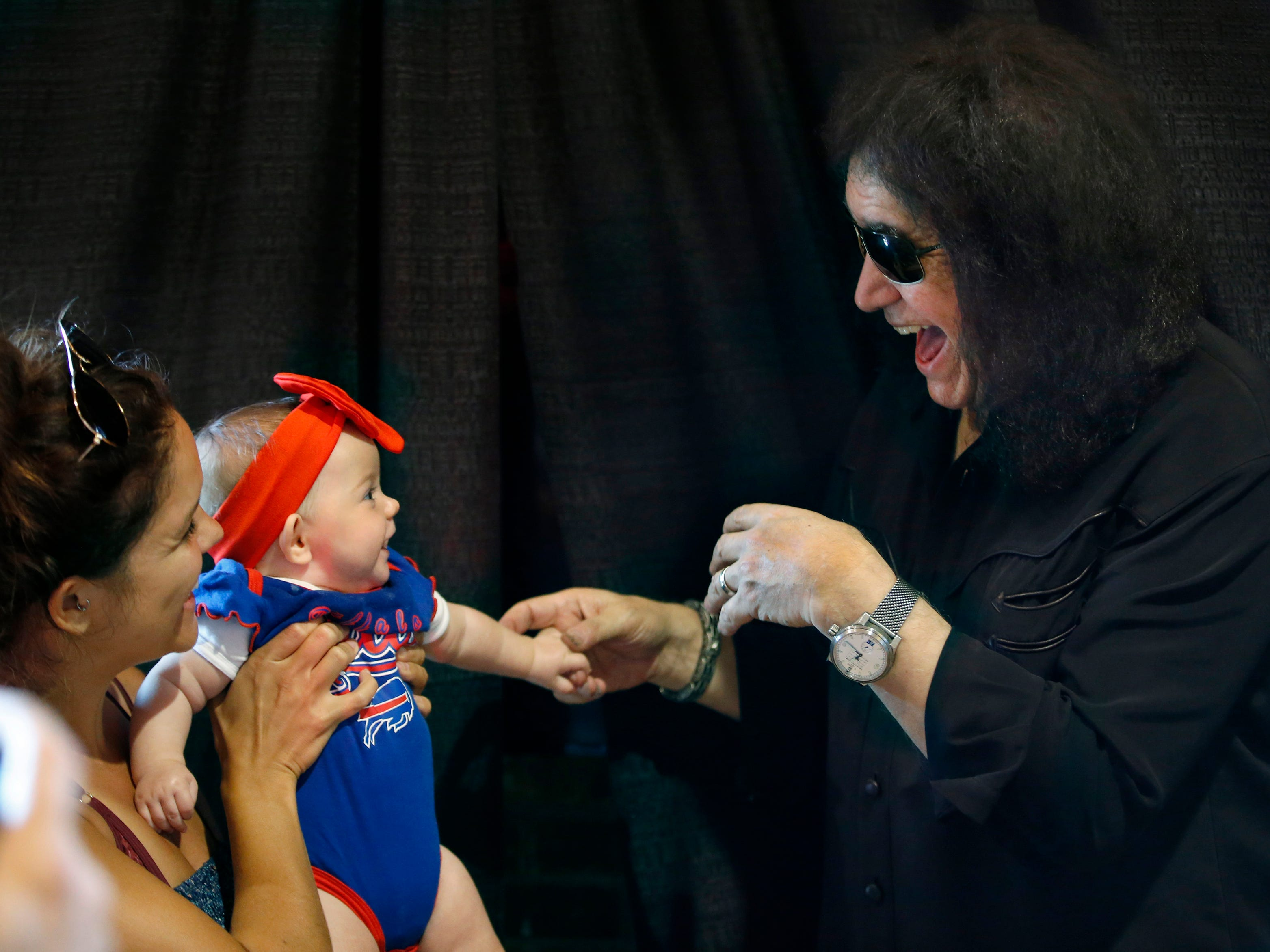 KISS co-founder Gene Simmons makes faces for five-month-old Layla Sager of Rochester who held by her mother Kirsten smiles back at him, during his appearance at the Chili-Paul Wegmans store to promote his MoneyBag Sodas.