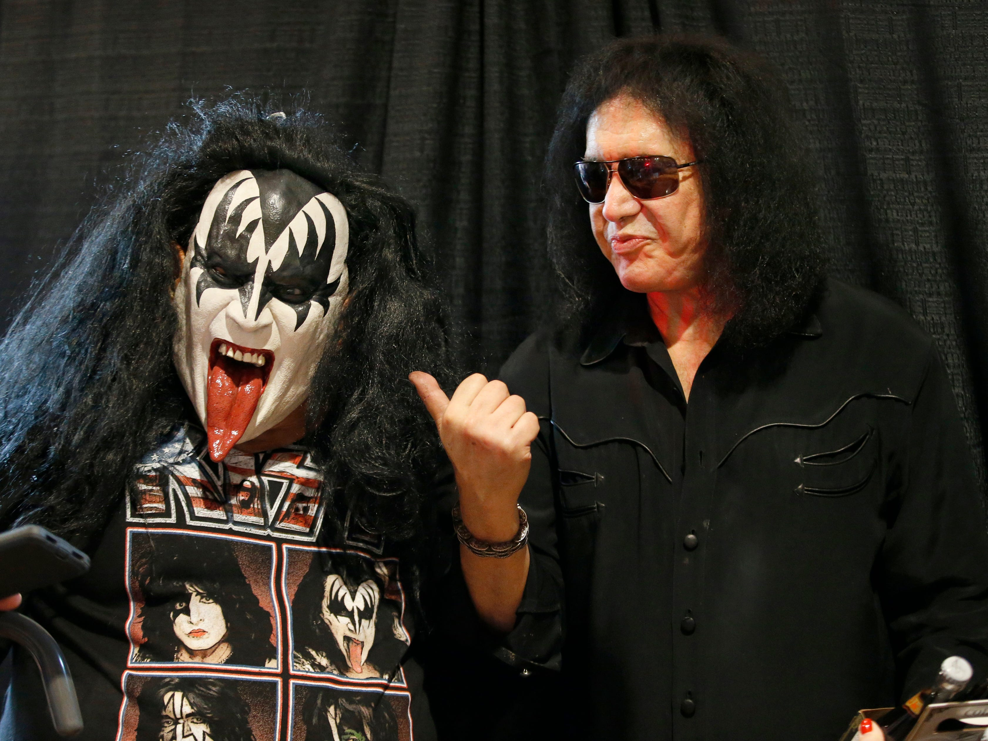Fan John Cook of Greece, wears a mask with the face of KISS co-founder Gene Simmons who made an appearance at the Chili-Paul Wegmans store to promote his MoneyBag Sodas.
