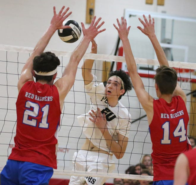 Penfield's Josh Coan, center, sends his spike into the blocking defense of Fairport's Matt Beiter, left, and Mitch Tucker, right, during their matchup Monday, Sept. 17, 2018 at Penfield High School.