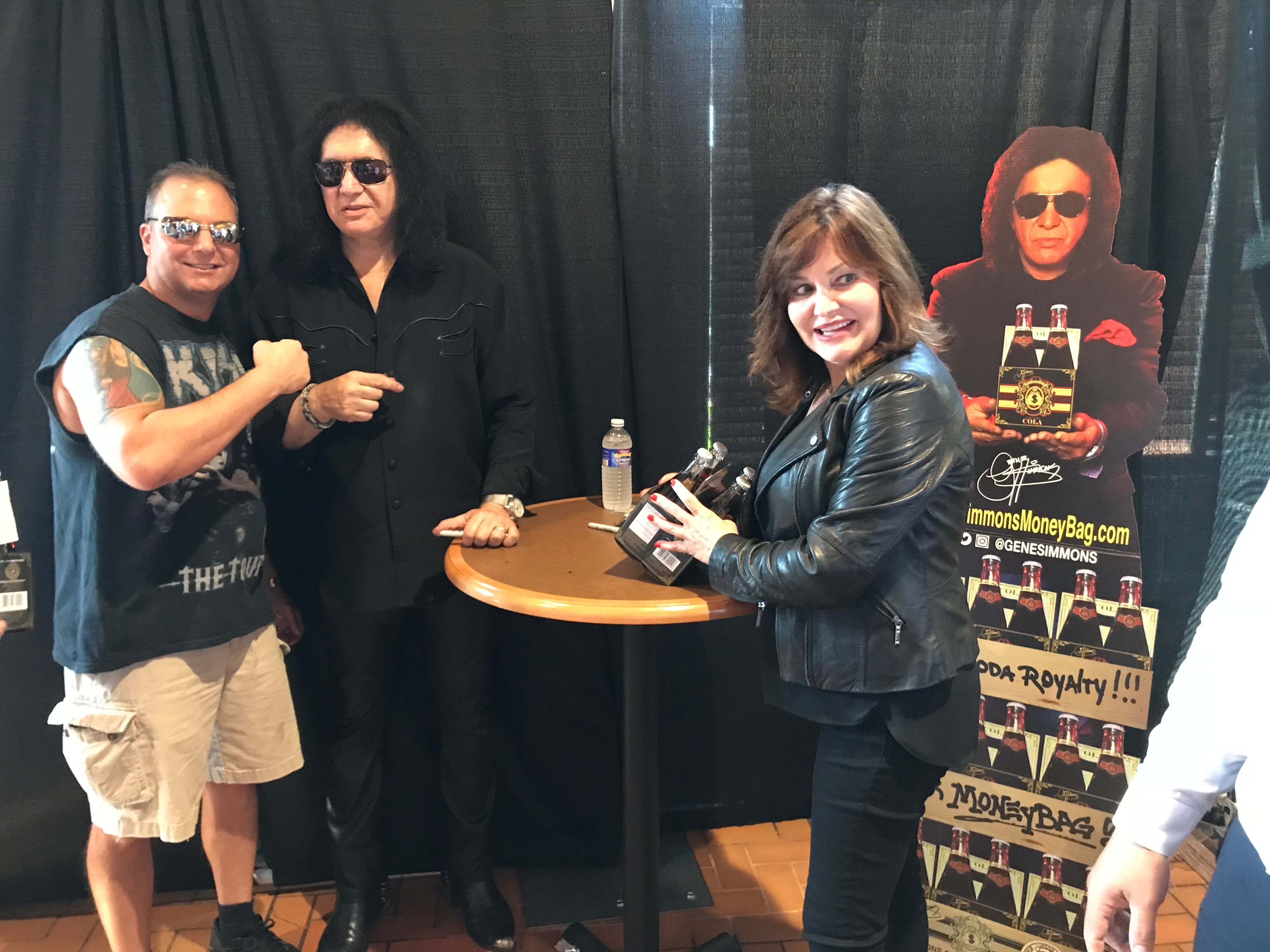 Gene Simmons poses with people near new soda line.
