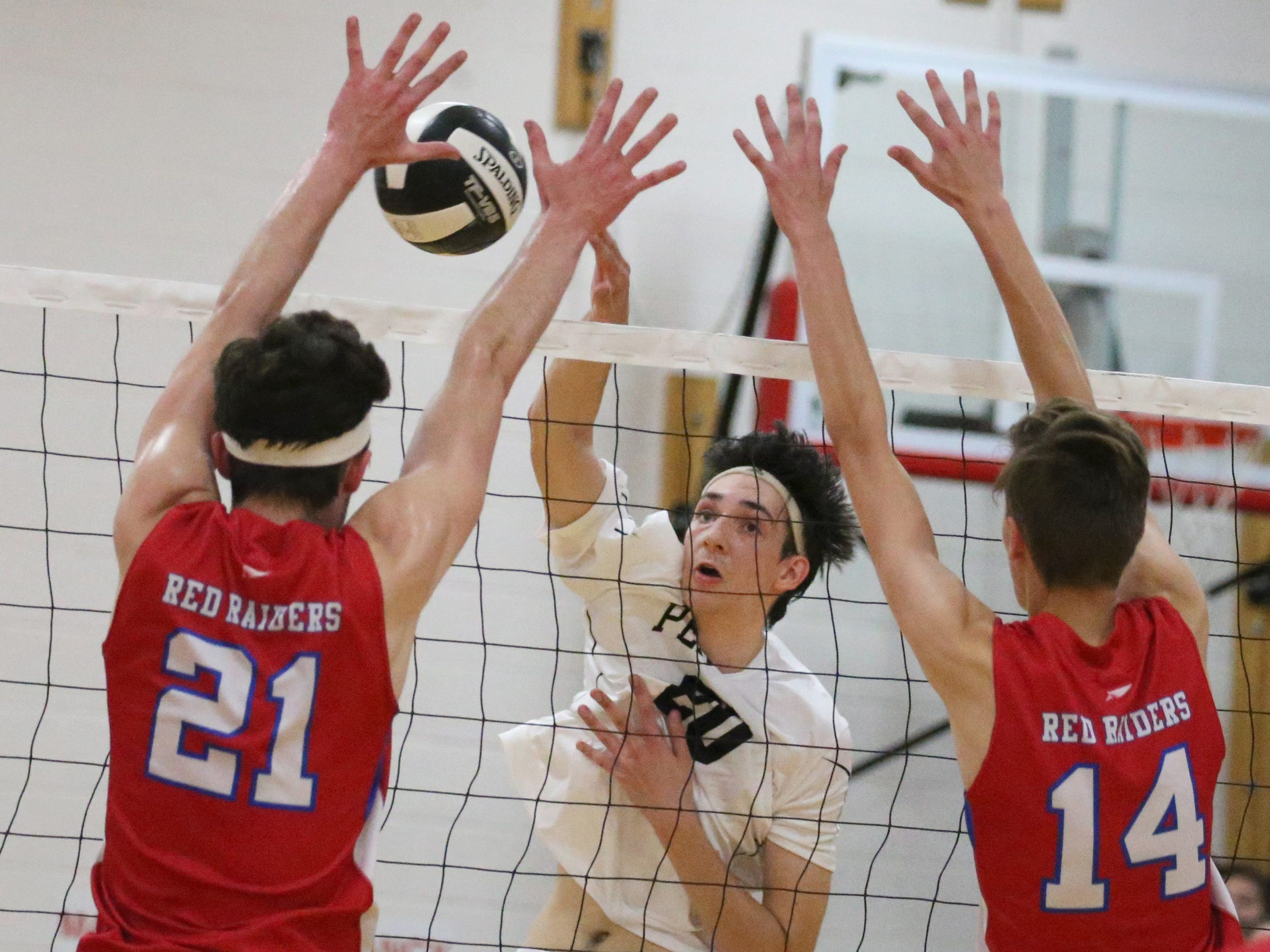 Penfield's Josh Coan, center, sends his spike into the blocking defense of Fairport's Matt Beiter, left, and Mitch Tucker, right.