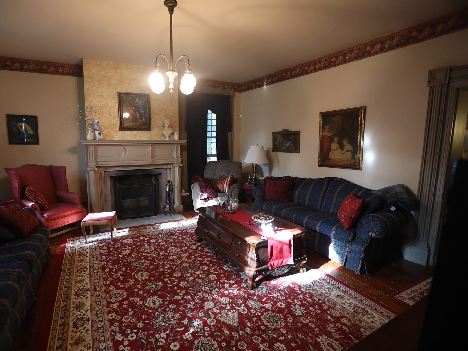 There are four fireplaces in the home; the living room is home to one of them.  The light fixtures in the living room, den, and hallway were originally gas lights but have been converted to electric.