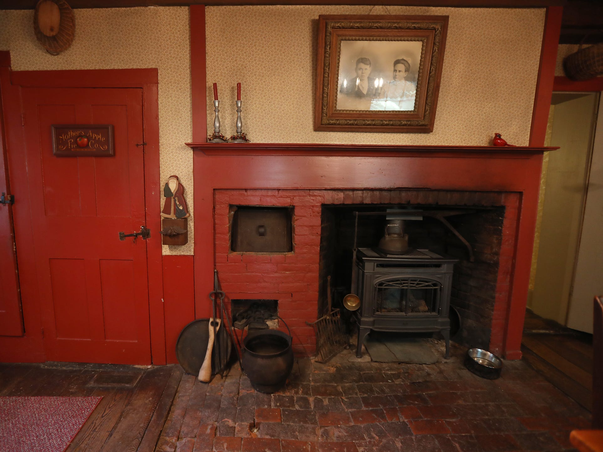 The home still has its original cooking fireplace with some of the hardware intact from early days. Above the fireplace is a picture of relatives of the Jewetts, the original owners.