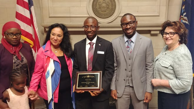 Alhassan Susso, a Poughkeepsie resident, was named Teacher of the Year for his work as a teacher in the Bronx.  He was honored Sept. 18, 2018. by the state Board of Regents with Education Commissioner MaryEllen Elia, right; his brother; Chancellor Betty Rosa and his wife and daughter.