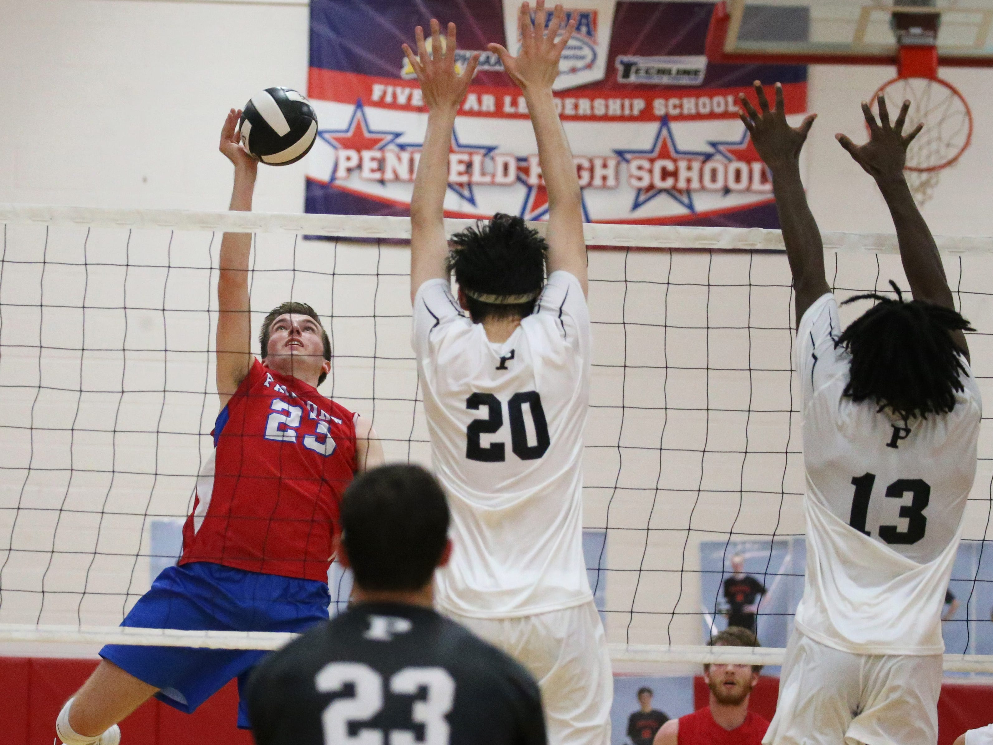 Fairport's Ryan Parker, left, sends in a spike past the defense of Penfield's Josh Coan, center, and Christian Allen, right.