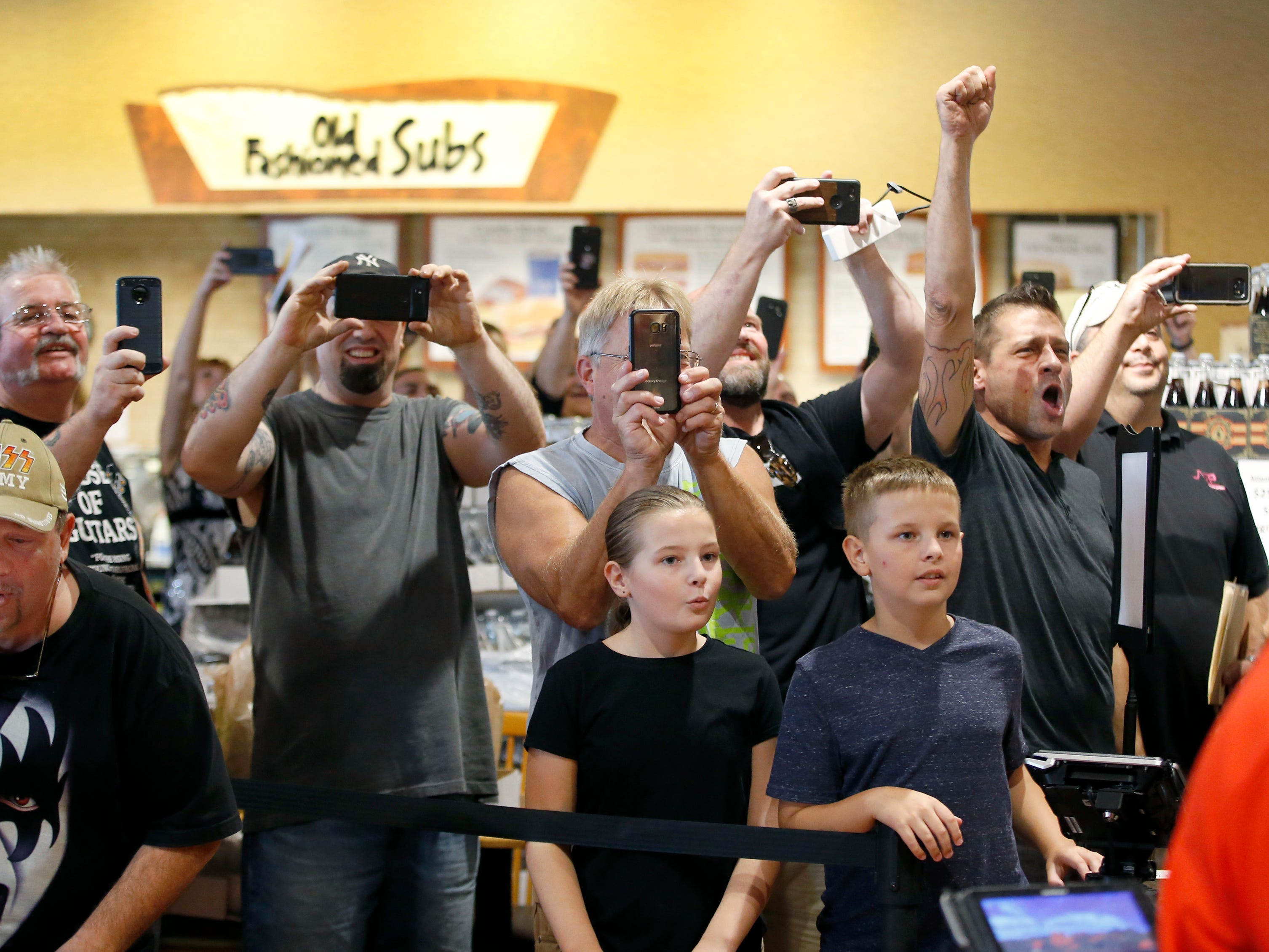 Fans take out the phones as soon as KISS co-founder Gene Simmons walks into the Chili-Paul Wegmans store to promote his MoneyBag Sodas.