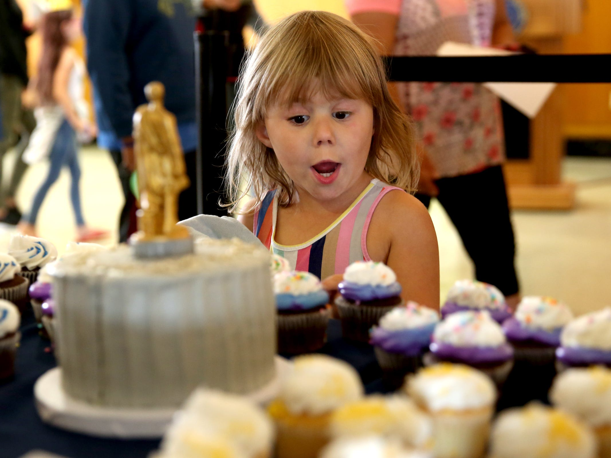 Cambria Nations, 5, of Salem, picks out a cupcake during an 80th birthday party for the Oregon Pioneer, aka the Gold Man, at the Oregon State Capitol in Salem on Tuesday, Sep. 18, 2018.