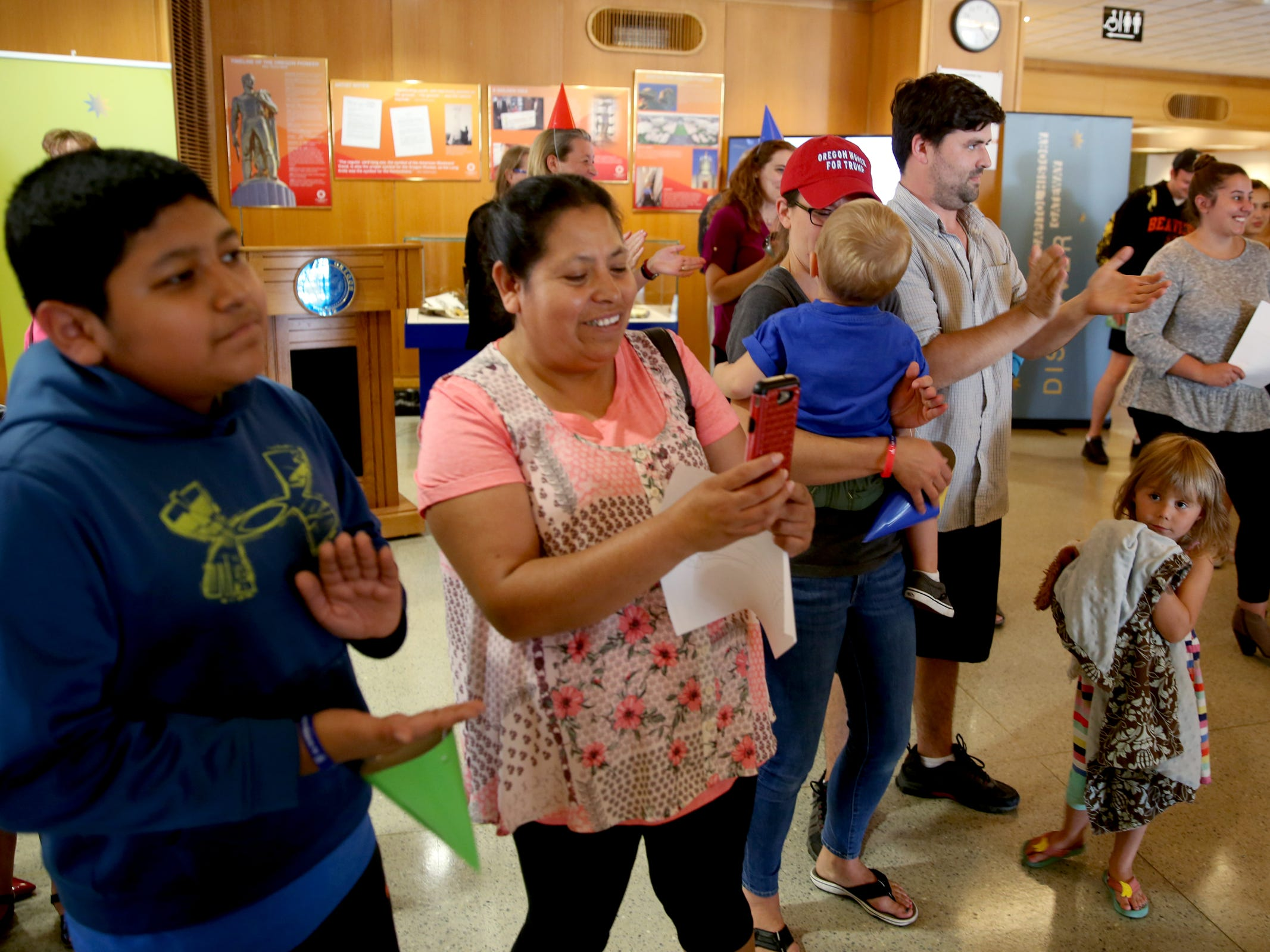 Julian Barrera, far left, 12, and his mom, Alicia Sagerro, of Salem, sings Happy Birthday during an 80th birthday party for the Oregon Pioneer, aka the Gold Man, at the Oregon State Capitol in Salem on Tuesday, Sep. 18, 2018.