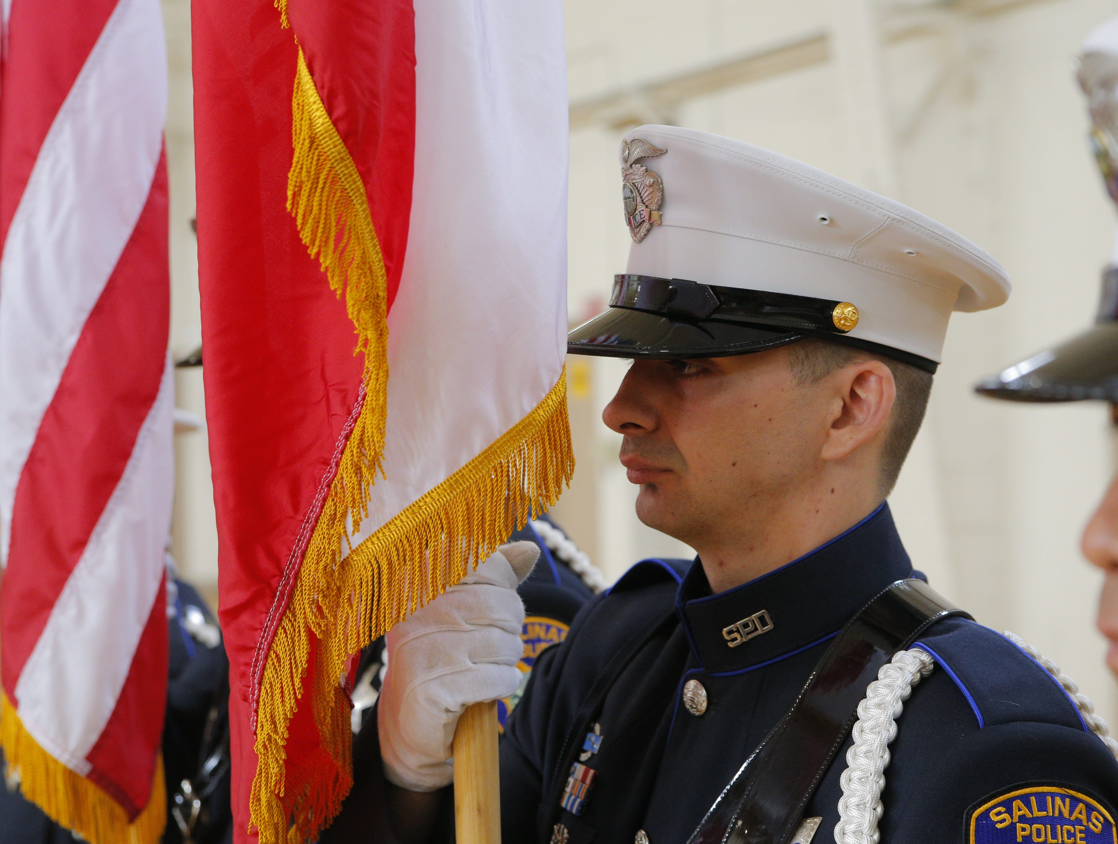 Salinas police officer and member of the color guard Clifton Smith prepares to present the flag Cmdr. Henry Gomez's retirement ceremony.