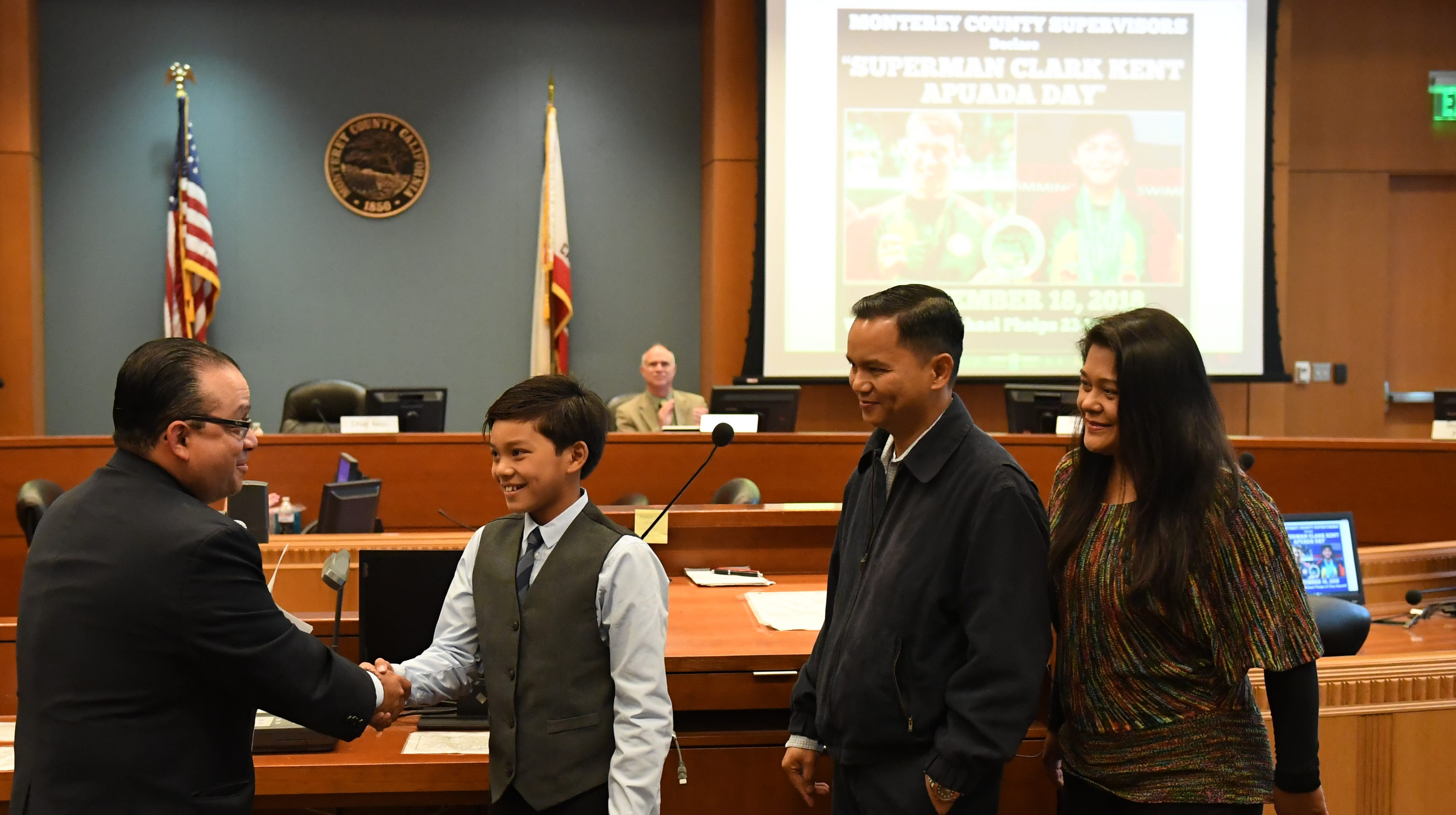 Ten-year-old Clark Kent Apuada (second from left) shakes hands with Monterey County Board of Supervisor Chair Luis Alejo (left) during the ceremony honoring Apuada's achievements.