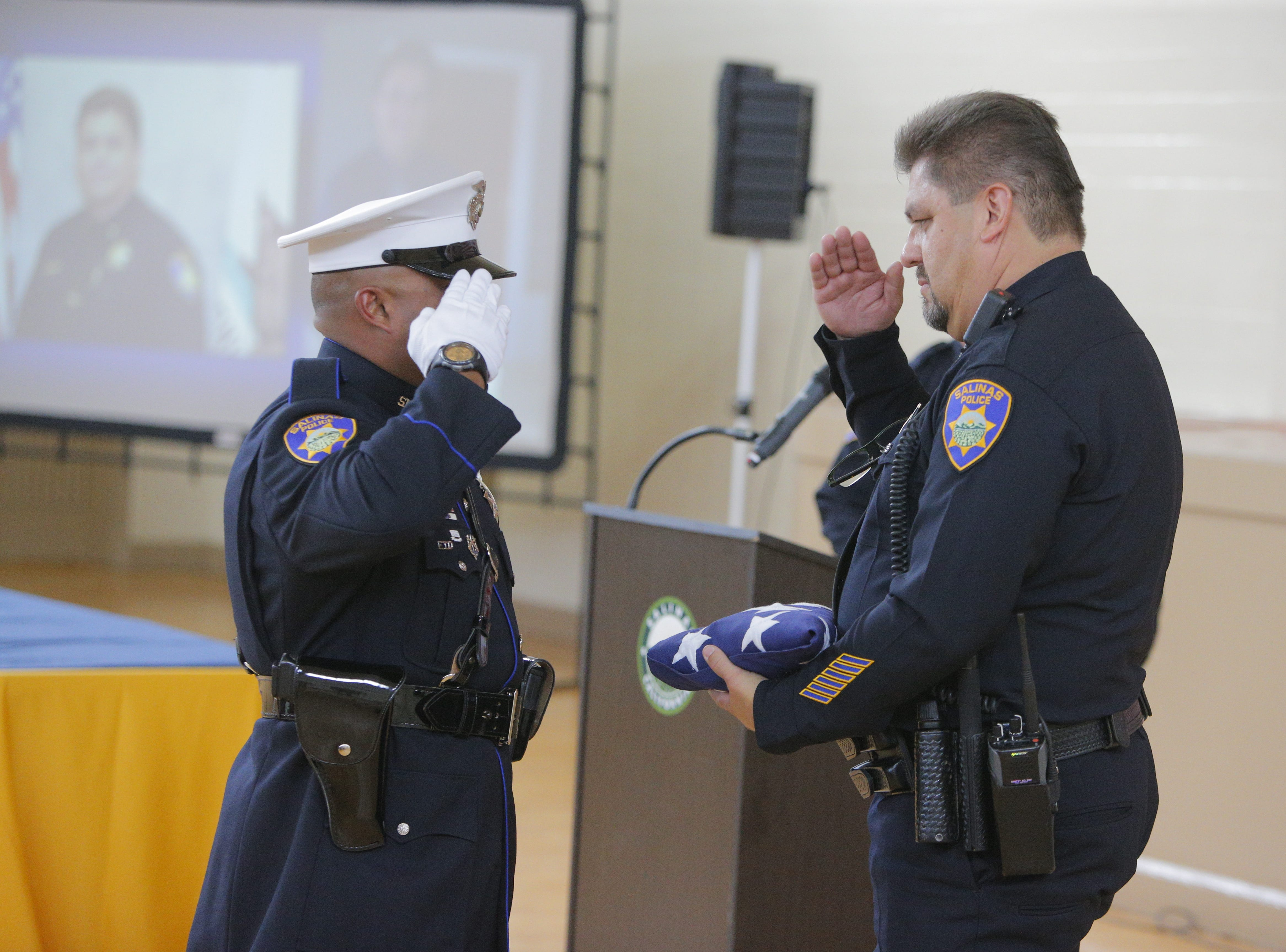 A Salinas police officer exchanges salutes with Cmdr. Henry Gomez after giving him a U.S. flag during his retirement  ceremony Tuesday.