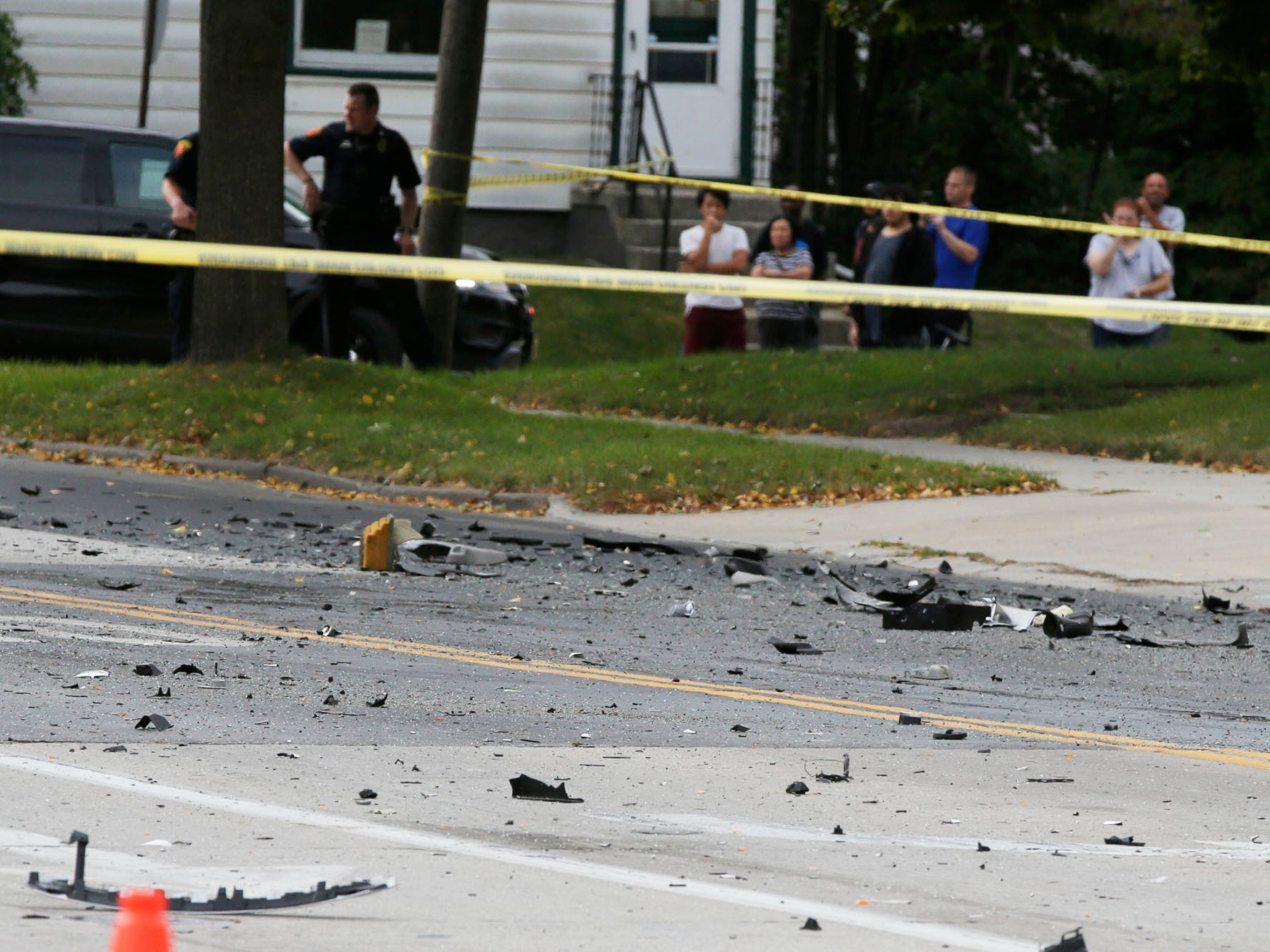 Debris is strewn at the scene of a 2-car crash on Pennsylvania Avenue between 14th and 15th streets, Tuesday, September 18, 2018, in Sheboygan, Wis. A third parked car was also struck. Two people died as a result of the crash.